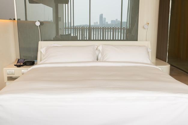 호텔 객실의 침대에 흰색 시트와 베개가있는 킹 사이즈 침대.