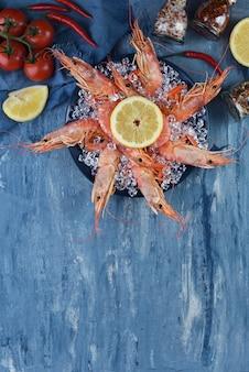 Королевские креветки на плите с льдом и лимоном на голубой предпосылке с космосом экземпляра. меню или рецепт морепродуктов. вид сверху креветок с овощами.