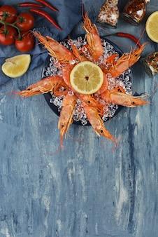Королевские креветки на плите с льдом и лимоном на голубой предпосылке с космосом экземпляра. меню или рецепт морепродуктов.