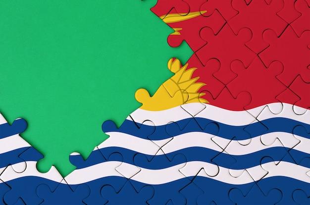 키리바시 깃발은 왼쪽에 무료 녹색 복사 공간이있는 완성 된 직소 퍼즐에 그려져 있습니다.