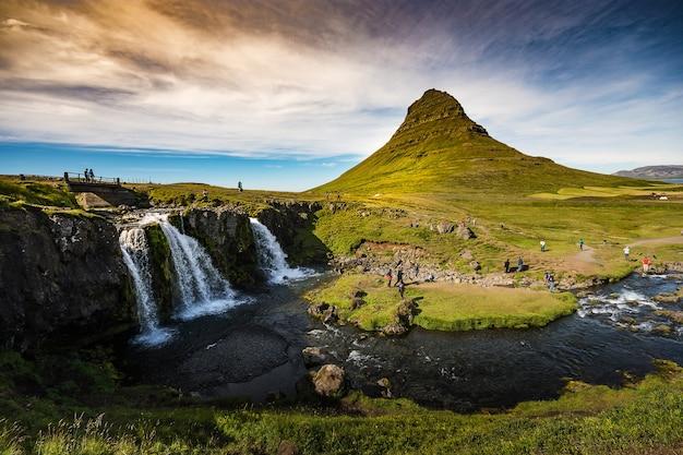 アイスランドのkirkjufell&kirkjufellfoss、緑の山、滝、明るい空を持つsu