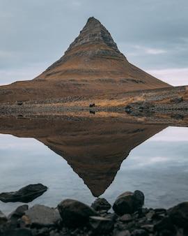 Гора киркьюфелл возле национального парка снафеллсйокудль, исландия, отражается в озере