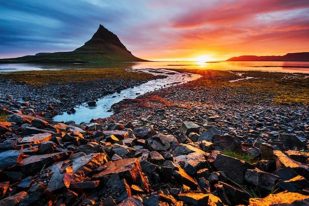 Живописный закат над пейзажами и водопадами. kirkjufell гора исландия