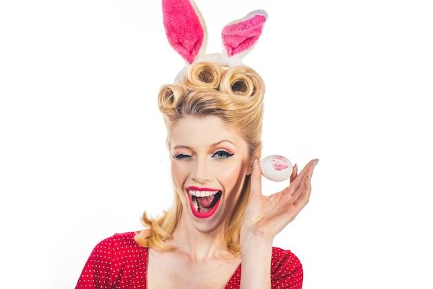 키스하고 윙크하십시오. 부활절 카드. 컬러 부활절 달걀으로 손. 부활절을 축 하하는 토끼 귀에 달콤한 사랑스러운 소녀.