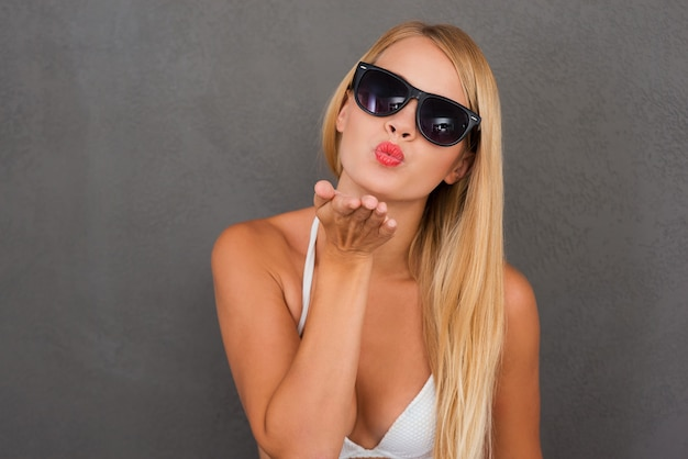 あなたにキスを!キスを吹く白いランジェリーで遊び心のある若い女性