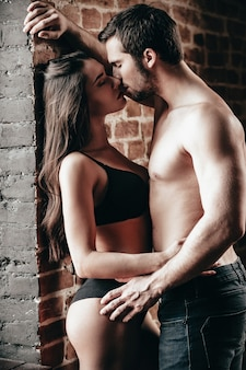 今私にキスしてください。レンガの壁の近くに立っている間キスと抱擁美しい若い上半身裸のカップルの側面図