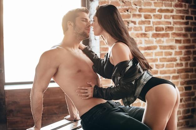 キスして!木製パレットに座っている彼女のボーイフレンドに寄りかかって完璧なお尻を持つ美しい若い女性の側面図