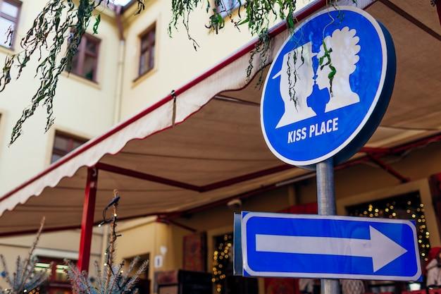 リヴィウの屋外カフェで場所の標識にキスします。キスカップルの写真と矢印。旅行と観光、興味のある場所