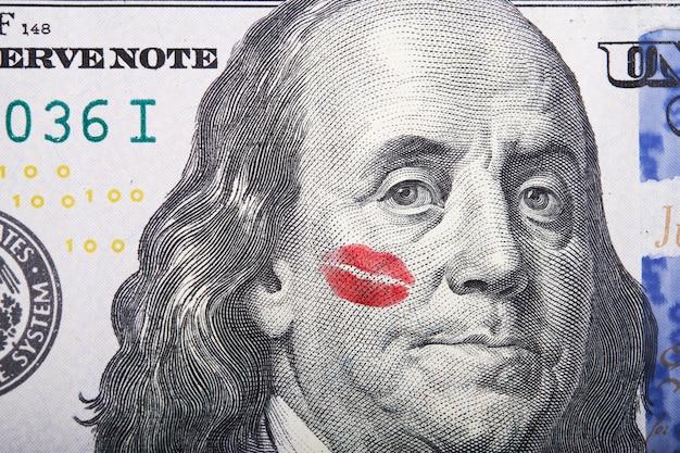 Kiss on portrait of benjamin franklin on a hundred dollar bill.