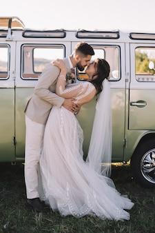 レトロカー近くの情熱的なカップルのキスと抱擁