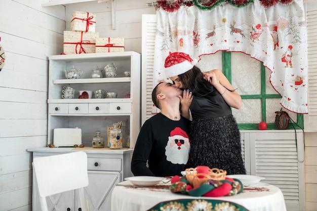 クリスマススタジオでポーズをとって美しいカップルにキス