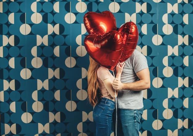 Kissing caucasian couple are hiding behind some air heart sharped balloons on a blue  wall