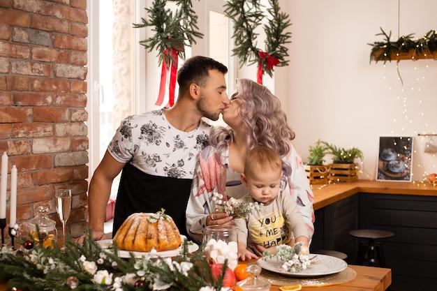クリスマスの魔法を楽しんでいるキッチンでカップルの家族にキスします。