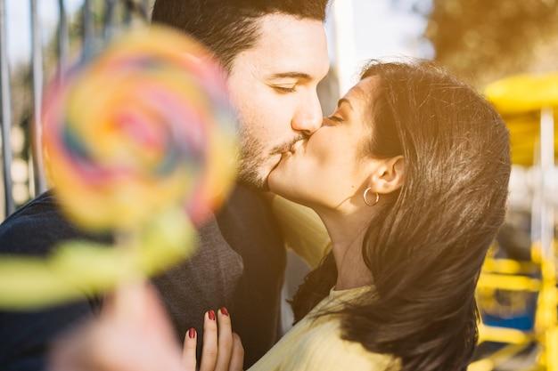 Kissing couple holding a lollipop