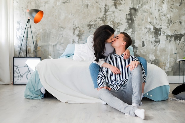 Kissing couple in industrial style bedroom