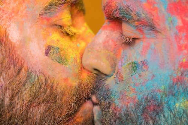 Kissing couple of rainbow painted homosexual men