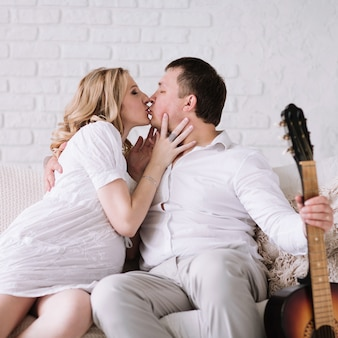 Kissing couple sitting on the couch in a cozy living room