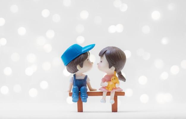 발렌타인 데이 빛나는 배경으로 나무 벤치에 앉아 키스 커플