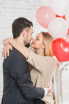 Kissing couple with heart-shaped balloons