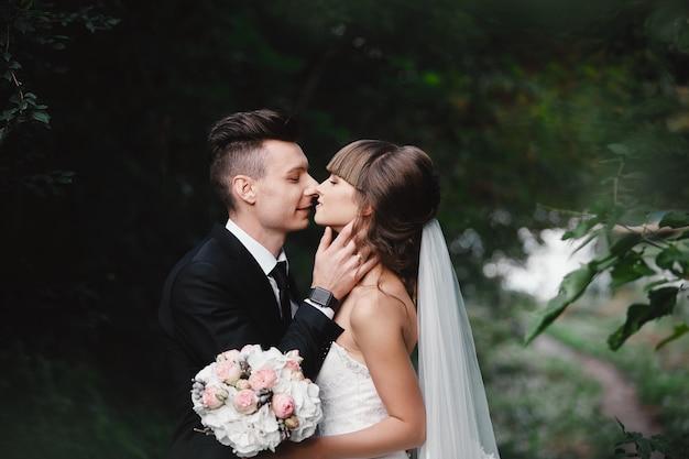 公園kissing.couple新婚の新郎新婦自然緑の森での結婚式で新郎新婦は写真の肖像画にキスしています。結婚式のカップル。新婚夫婦。