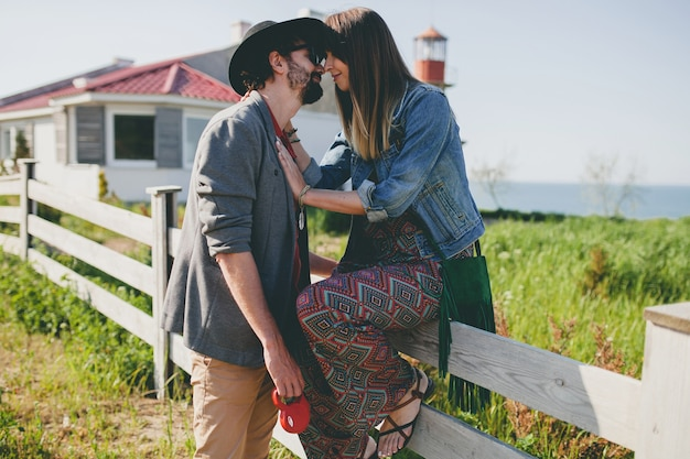 Kissing happy young stylish hipster couple in love walking in countryside, summer style boho fashion