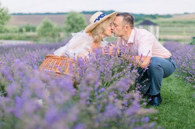 우아한 세련된 옷을 입은 성숙한 부부에게 아름다운 꽃이 만발한 라벤더 밭에 앉아 키스