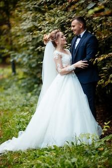 Жених и невеста в парке kissing.pou новобрачные жених и невеста на свадьбе в природе зеленый лес целуются фото портрет. свадебные пары