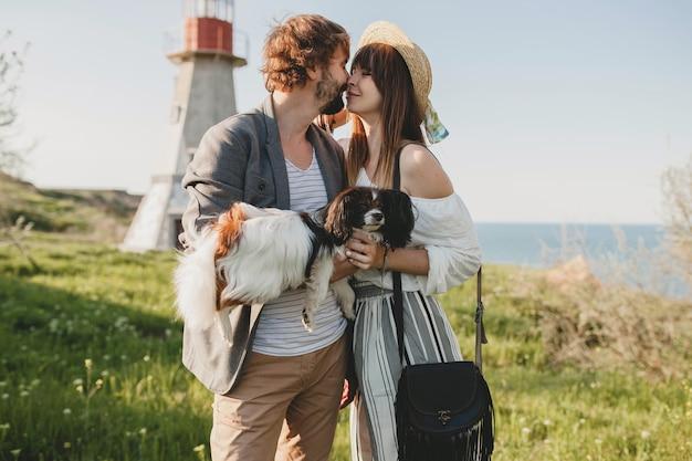 Целующаяся стильная хипстерская влюбленная пара гуляет с собакой в сельской местности, летняя мода в стиле бохо, романтика