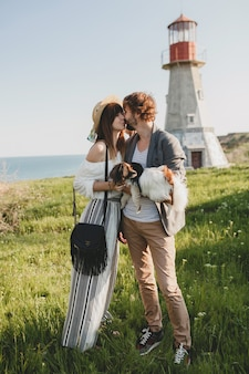Целующаяся стильная хипстерская влюбленная пара гуляет с собакой в сельской местности