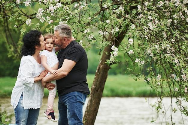 아이에게 키스. 손녀와 함께 좋은 주말을 야외에서 즐기는 명랑 커플. 좋은 봄 날씨