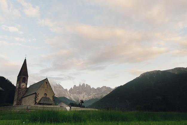 Поцелуй свадебной пары стоит перед каменной церковью в горах