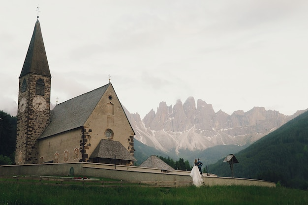 Kissing wedding couple stands before stone church in mountains