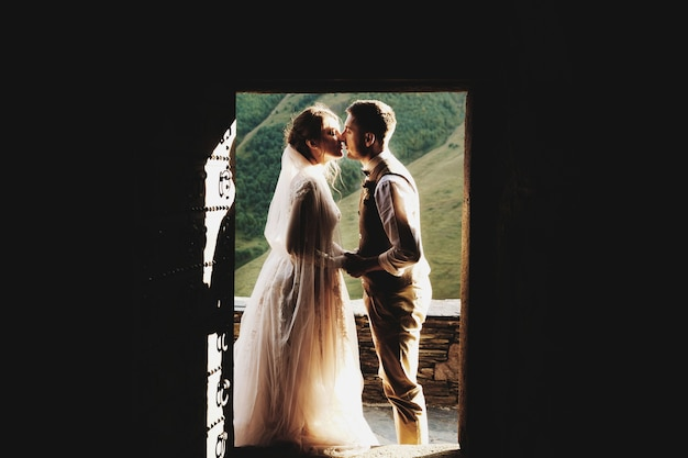 Kissing wedding couple stands in the doors before beautiful mountains in georgia