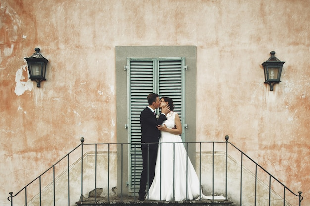 Kissing wedding couple stands on the footsteps before an orange italian villa