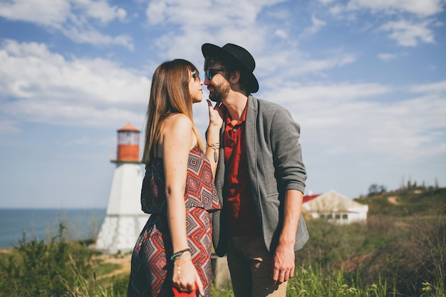 Kissing young hipster couple indie style in love walking in countryside, lighthouse on background
