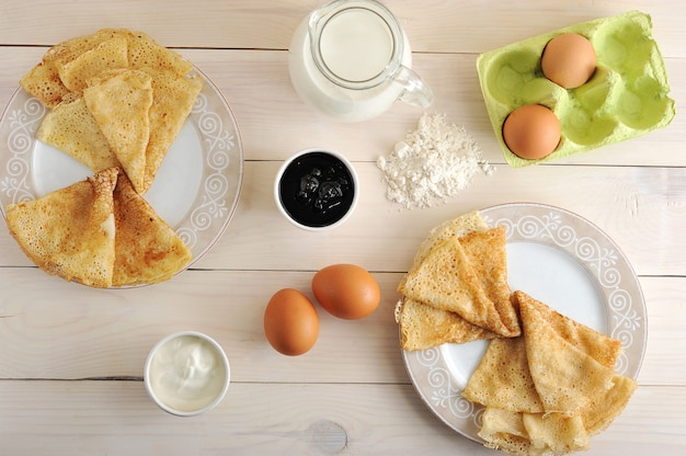 A kit for making pancakes, eggs, milk, pitcher, flour, sour cream and jam
