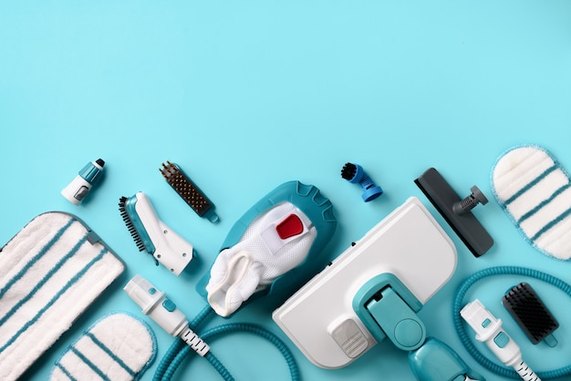 Kit of modern professional steam cleaners on blue background.