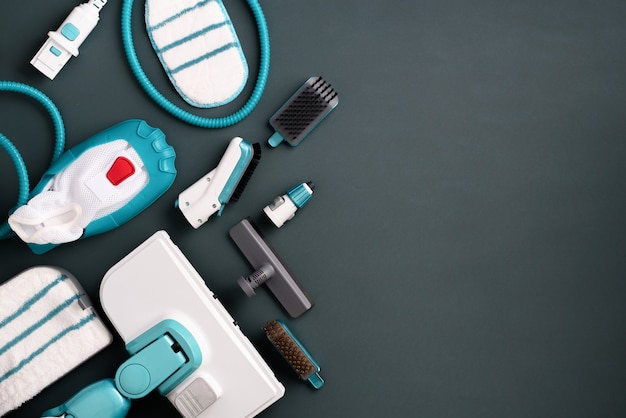 Kit of modern professional steam cleaners on grey background.