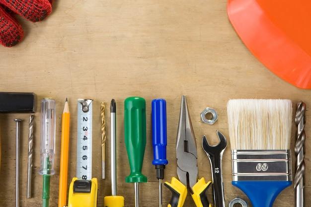 木の質感の背景に建設ツールと楽器のキット