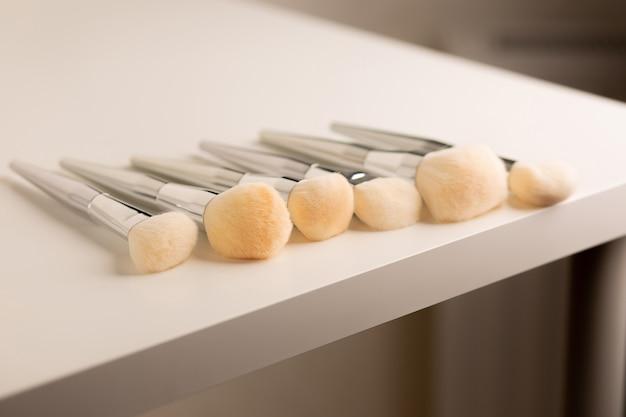 Набор кистей для макияжа лица для пудры, хайлайтера, бронзатора и румян лежит на рабочем столе.
