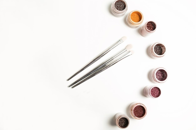 Набор минеральных теней для век, блеска и кистей для макияжа на белом фоне. место для текста