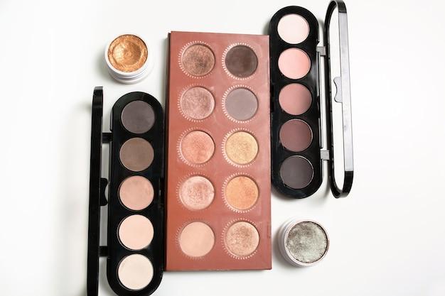 Набор профессиональных палитр макияжа телесного цвета с кремовыми тенями для век на белом фоне