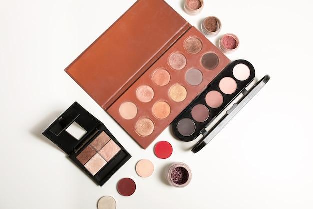 Набор профессиональных палитр для макияжа телесного цвета с рассыпчатыми тенями на белом фоне.