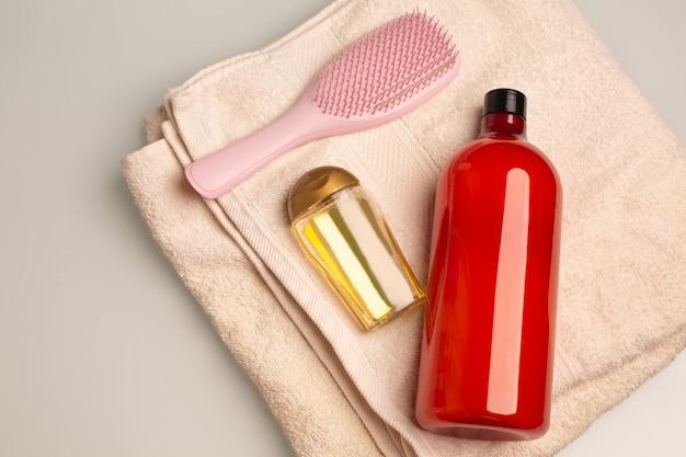 バスルームのバスタオルの上に横たわるシャンプー、トリートメントヘアオイル、コームのキット。テキスト用のスペース