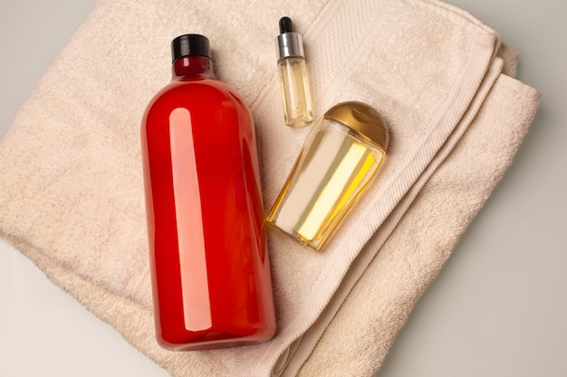 バスルームのバスタオルの上に横たわるシャンプー、トリートメントヘアオイル、美容液のキット。テキスト用のスペース