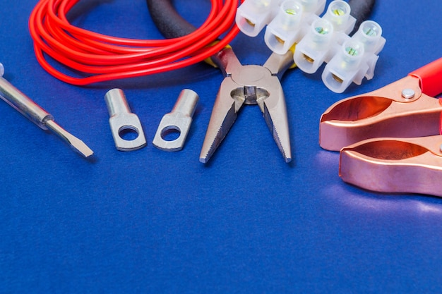 Kit spare parts and tools, red wires for electrical prepared before repair or setting on blue workshop table