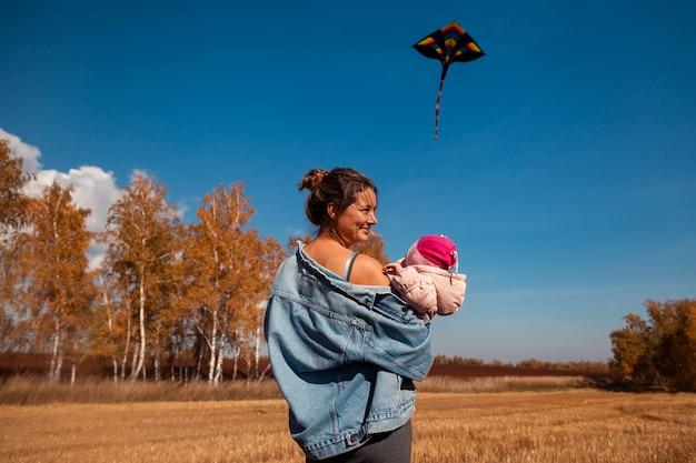 赤ちゃんと若い妊婦は自然を楽しんで、暖かい秋の晴れた日にkitで遊ぶ