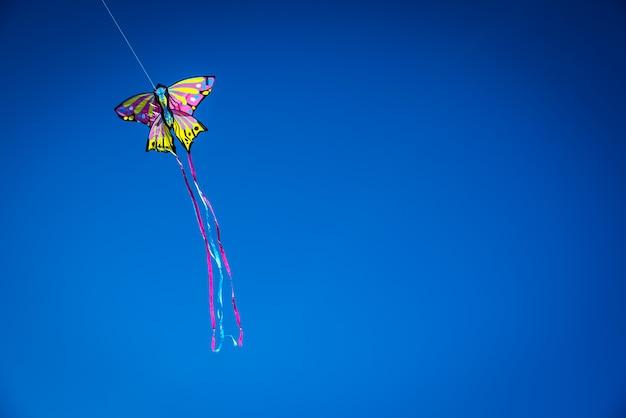 コピーのための負の空間、青い空を飛んでいるカラフルなkit。
