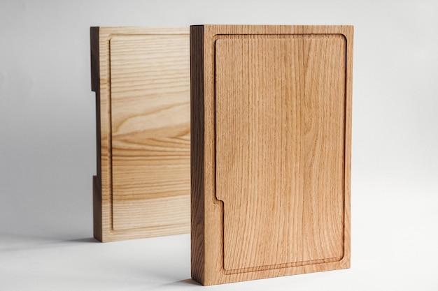 キッチンと台所用品。素朴でラフな食器や調理器具。白い壁のそばの2つの荒い木製のまな板。カントリースタイル。木製の手作り食器。白色の背景。