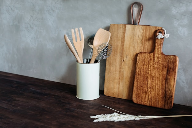 Kitchen appliances.metal and wooden. fork, spoon, and spatula on a wooden table top, against a gray textured wall.